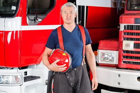 fire fighter: Portrait of confident mature fireman holding red helmet against firetrucks at station