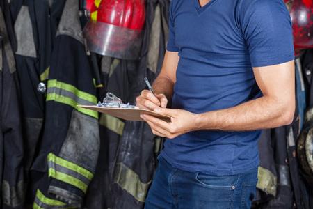 bombero: Secci�n media de bombero escrito en el portapapeles en la estaci�n de bomberos