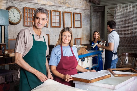 deckle: Portrait of smiling man and woman making papers with colleagues in factory