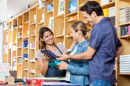 Happy saleswoman showing books to mid adult couple in shop