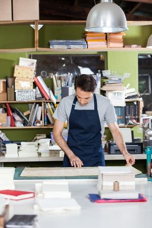 obrero trabajando: Mediados de adultos trabajador masculino para trabajar en la mesa en la fábrica de papel Foto de archivo