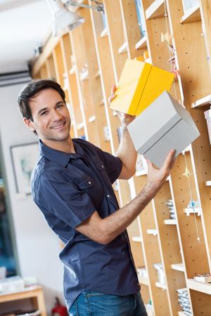 removing: Side view portrait of smiling male customer removing cardboard boxes from shelf in shop Stock Photo