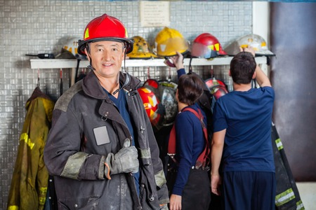 fireman: Portrait of smiling mature fireman at fire station with team in background Stock Photo