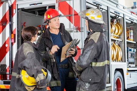 firefighter: Bomberos masculinos y femeninos en discusiones de pie sobre cami�n en la estaci�n de bomberos Foto de archivo