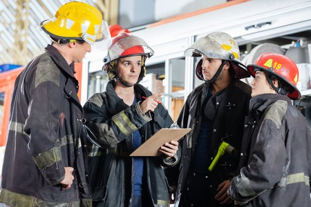 emergency: Male firefighter gesturing while discussing with colleagues at fire station