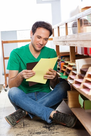 mid adult male: Mid adult male customer holding papers by shelf in shop