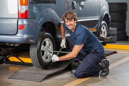 mecanico: Retrato mec�nico de confianza masculina con una llave para fijar la llanta del neum�tico de coche en el taller de reparaci�n de autom�viles