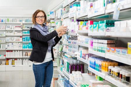 Portrait of smiling mid adult female customer choosing product at pharmacy 版權商用圖片