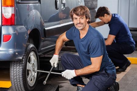 auto repair: Portrait of confident male mechanic fixing car tire at auto repair shop