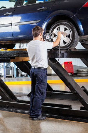 tire service: Full length of mechanic examining gauge while inflating car tire at garage