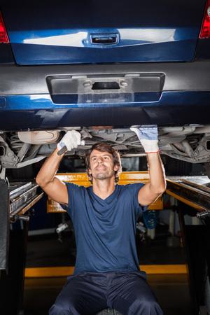 mecanico: Mecánico de sexo masculino levantó debajo del coche en el garaje