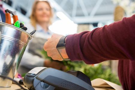 pagando: Imagen recortada de cliente femenina pagar a través de reloj inteligente en la tienda de flores