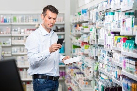 adult male: Mid adult male customer checking information on mobile phone while holding product in pharmacy Archivio Fotografico