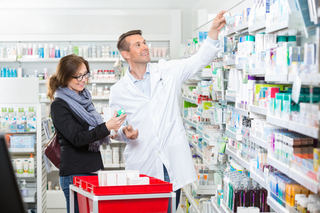 labcoat: Smiling male chemist in labcoat removing medicine for female customer in pharmacy