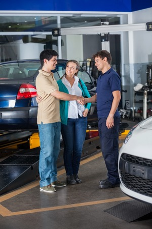 auto repair: Confident mechanic shaking hand with couple at auto repair shop