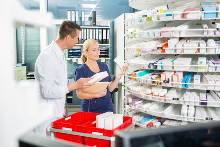 Male pharmacist counting stock with female assistant in pharmacy