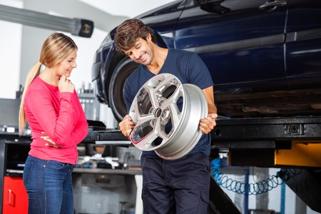 woman shop: Happy mechanic showing metallic alloy to female customer at garage