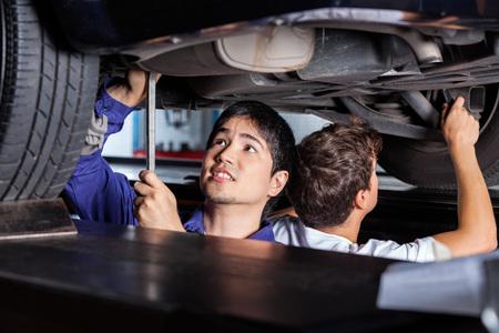mecanico: Mec�nicos de sexo masculino que trabajan bajo el coche levantado en el garaje