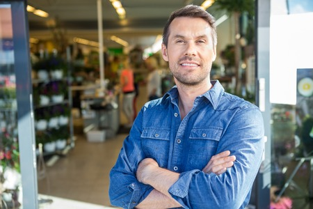 Portrait of confident man with arms crossed standing outside flower shop