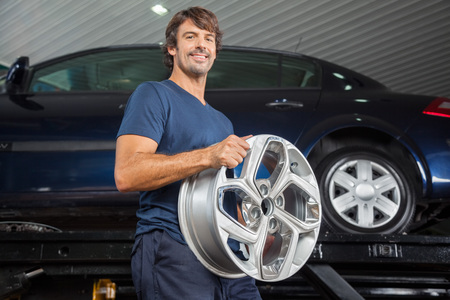 mag: Low angle portrait of smiling technician holding metallic alloy at auto repair shop