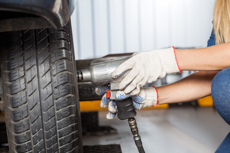 pneumatic: Cropped of female mechanic using pneumatic wrench to fix car tire at repair shop