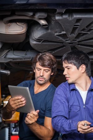 mecanico: Mecánicos de sexo masculino que usa la tableta digital de bajo el coche levantado en el garaje