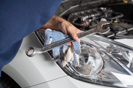 Cropped image of male mechanic holding wrench and gloves by car engine at auto repair shop