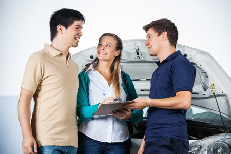 technicians: Happy couple discussing with mechanic while signing on document at garage