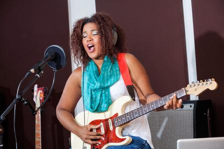 musico: Joven apasionado cantante tocando la guitarra en el estudio de grabación