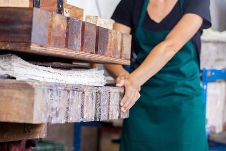 mid adult female: Midsection of mid adult female worker using paper press machine in factory Stock Photo