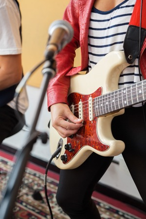 signer: Midsection of female signer playing guitar in recording studio