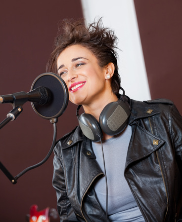 hair band: Smiling young woman singing while looking away in recording studio