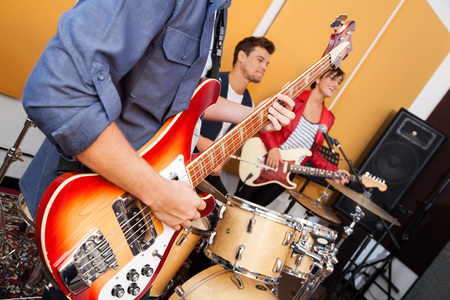 midsection: Midsection of male guitarist performing with band in recording studio Stock Photo