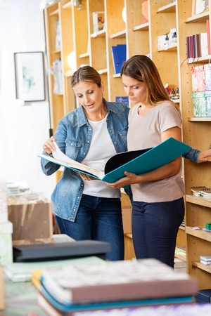 mid adult   female: Mid adult female friends looking at large book in store Stock Photo