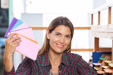 paper art: Portrait of smiling woman holding colorful papers in shop