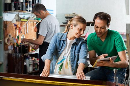 usando computadora: Mediados supervisor adulto de sexo masculino que muestra el diseño en el ordenador tableta para empleada usando la escobilla de goma en la fábrica de papel Foto de archivo