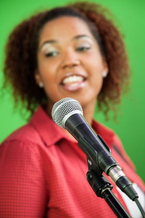 microphone: Young woman singing with focus on microphone in recording studio