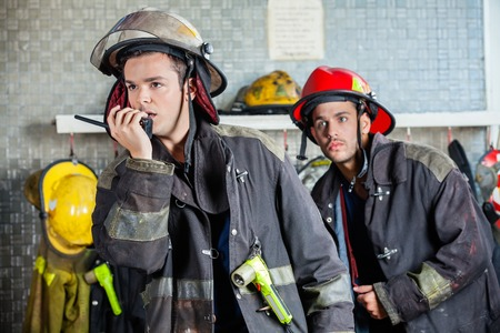 fire fighting equipment: Male firefighter using walkie talkie at fire station with colleague standing in background