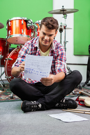 composer: Happy young male drummer writing notes on paper while sitting on floor in recording studio