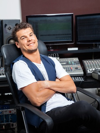 masters of rock: Portrait of relaxed young man sitting arms crossed at mixing table in recording studio Stock Photo
