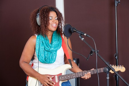 niñas jugando: cantante joven con los ojos cerrados a tocar la guitarra en el estudio de grabación