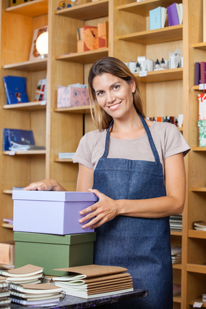woman shop: Portrait of confident mid adult female worker with cardboard boxes in store