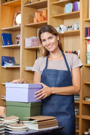 mujer trabajadora: Retrato de confianza trabajadora medio adulto con cajas de cartón en la tienda
