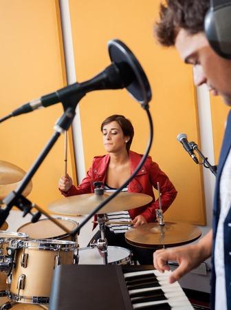 pianista: batería de sexo femenino joven que se realiza con el pianista de sexo masculino en el estudio de grabación Foto de archivo