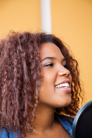 young woman: Closeup of young woman with curly hair singing in recording studio