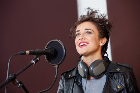 spiked hair: Happy young woman singing while looking away in recording studio