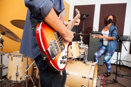 young musician: Midsection of man playing guitar while woman singing and dancing in background at recording studio