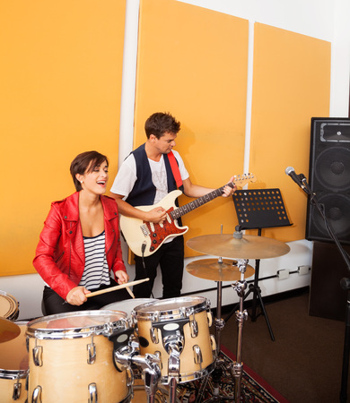 drummer: Happy female drummer and male guitarist performing in recording studio