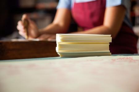 obrero trabajando: Primer de papeles apilados en la mesa con la trabajadora trabajan en segundo plano Foto de archivo