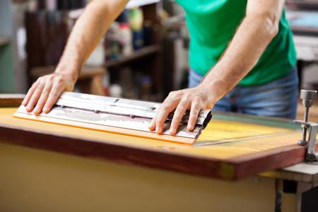 공장에서 스퀴지를 사용하는 중반 성인 근로자 스톡 콘텐츠